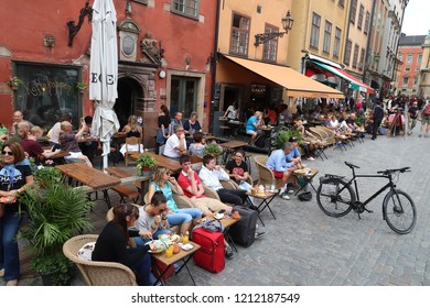STOCKHOLM, SWEDEN - AUGUST 23, 2018: People visit Stortorget square cafe in Gamla Stan (Old Town) in Stockholm, Sweden. Stockholm is the capital city and most populous area in Sweden.