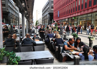 STOCKHOLM, SWEDEN - AUGUST 23, 2018: People visit restaurant at Drottninggatan shopping street in Norrmalm district, Stockholm, Sweden. Stockholm is the capital city and most populous area in Sweden.