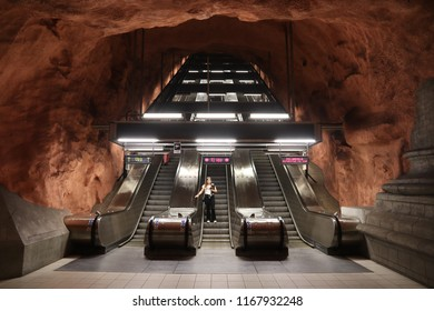 STOCKHOLM, SWEDEN - AUGUST 24, 2018: Person rides escalator in Stockholm metro (T-bana) underground station in Sweden. Stockholm metro is known for its artistic station interiors.