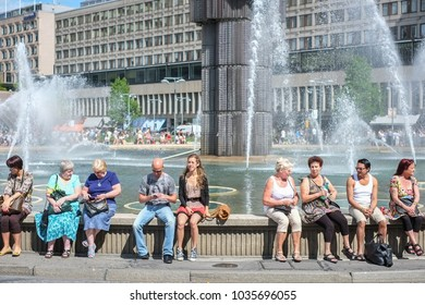STOCKHOLM, SWEDEN - AUGUST 4: People waiting by the Sergel fountain for Stockholm Pride Parade to begin on August 4, 2012 in Stockholm. The glass obelisk in the fountain was installed in 1974.