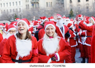 STOCKHOLM, SWEDEN - DEC 10, 2017: Smailing female Santas in traditional red dresses and beard in the Stockholm Santa Run in Sweden, December 10, 2017