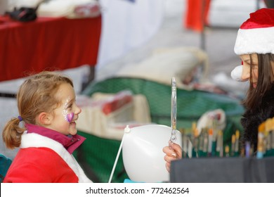 STOCKHOLM, SWEDEN - DEC 10, 2017: Smailing Santa kid when she see her face painting in the Stockholm Santa Run in Sweden, December 10, 2017