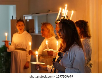 STOCKHOLM, SWEDEN - DEC 13, 2018: Lucia parade with singing girls in white dresses holding candles. Traditional celebration  of saint Lucia from Italy in Stockholm, Sweden, December 13, 2018
