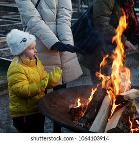 STOCKHOLM, SWEDEN - DEC 17, 2017: Girl warming her hands at the fire at the Christmas Fair and fire show at Rosendal Garden in Stockholm, Sweden, December 17, 2017