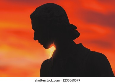 STOCKHOLM, SWEDEN - DEC 30, 2016: Face silhouette of statue of Carl von Linne at Waldermarsudde in colorful red sunset light.