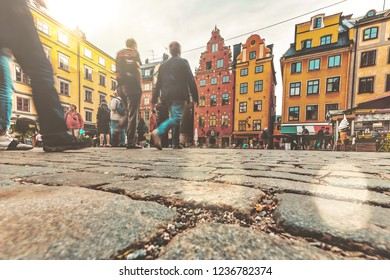 STOCKHOLM, SWEDEN - DEC 30, 2016: People walking at Stortoget in the old town of Stockholm with colorful facades. Low angle view