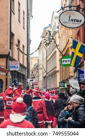 STOCKHOLM, SWEDEN -DECEMBER 11, 2016: People dressed up as santas run through the Old Town of Stockholm, participating in charity event Stockholm Santa Run in Sweden
