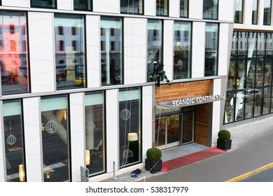 Stockholm, Sweden - December 17, 2016: climber hanging from ropes washes windows at the Scandic Continental, vasagatan 11 in Stockholm