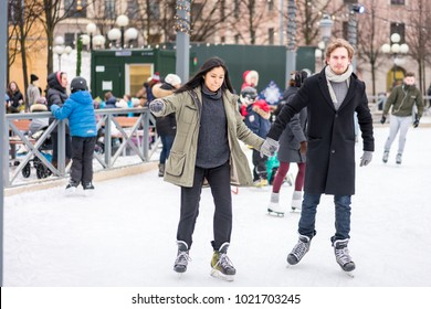 STOCKHOLM, SWEDEN - FEBRUARY 03, 2018: Front view of a young couple skating at a public ice skating rink outdoors in the city center of Stockholm february 03, 2018. Incidental people in the background