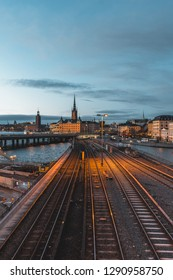 Stockholm, Sweden - January 1 2019: Evening cityscape with subway train crossing the bridge of Gamla Stan, Stockholm, Sweden. City hall and cathedral in background