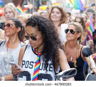 STOCKHOLM, SWEDEN - JUL 30, 2016: Afro woman wearing a rainbow tie and others in the Pride parade in the Pride parade July 30, 2016 in Stockholm, Sweden