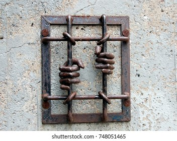 STOCKHOLM, SWEDEN - JULY 10, 2012: Prison bars and hands. Urban sculpture in Stockholm, Sweden