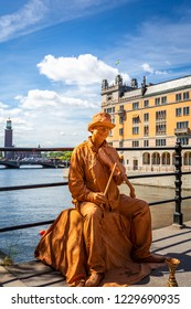 STOCKHOLM, SWEDEN - JULY 11, 2014: Outdoor closeup of a male street performer on a bridge wearing makeup and gold colored clothing playing an instrument in Stockholm Sweden July 11, 2014.