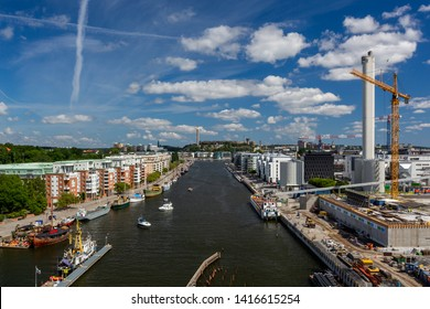 STOCKHOLM, SWEDEN - JULY 11, 2014: Panoramic view of a wide water canal with surrounding residential buildings and construction site against blue sky in Stockholm Sweden July 11, 2014.