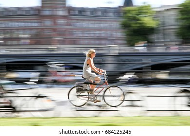 STOCKHOLM, SWEDEN – JULY 15, 2013: Young cyclist riding her bicycle close to the city center of Stockholm in a hot summer day.