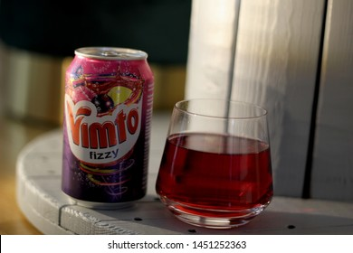 Stockholm, Sweden - July 15, 2019;  a glass of Vimto Fizzy next to a Vimto Fizzy can