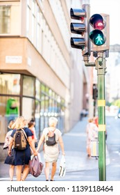 STOCKHOLM, SWEDEN - JULY 16, 2018: Back view of a traffic light with pedestrian sign and women crossing a street in Stockholm Sweden July 16, 2018.