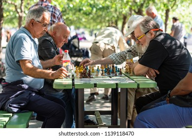 STOCKHOLM, SWEDEN - JULY 16, 2018: Selective focus side view of older men playing chess in a city square in Stockholm Sweden July 16, 2018. Incidental people in the background.