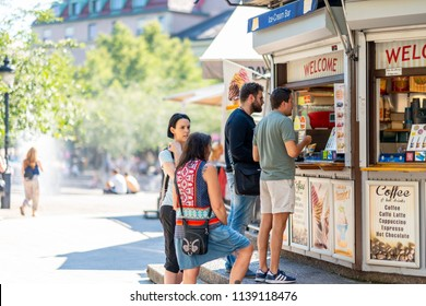 STOCKHOLM, SWEDEN - JULY 16, 2018: Selective focus side view of two woman and two men buying ice-cream at an outdoor ice-cream bar in a city square in Stockholm Sweden July 16, 2018.