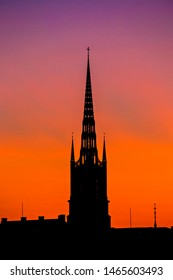 STOCKHOLM, SWEDEN - July 2019: Silhouettes of spires against sunset sky. Spire of Riddarholmskyrkan church, Stockholm, Sweden