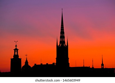 STOCKHOLM, SWEDEN - July 2019: Silhouettes of spires against sunset sky. Spire of Riddarholmskyrkan church and city Hall, Stockholm, Sweden