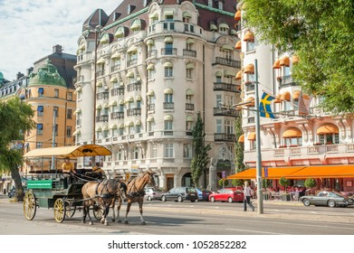 STOCKHOLM, SWEDEN - JULY 22, 2011: Horse cart at fashionable waterfront street Strandvägen in Stockholm. Some of the most expensive apartments in Sweden are located on this street.