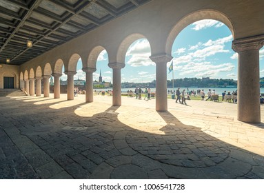 Stockholm, Sweden - July 22, 2013: View on city hall (stadshuset) building. Stockholm, Sweden, Scandinavia, Europe. Arches in foreground, cityscape and sky in background.