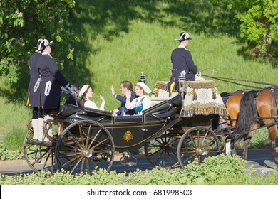 STOCKHOLM, SWEDEN - JUN 06, 2017: The swedish princess and prince Sofia and Carl Philip, Madeleine and Chris Bernadotte smiling and waiving to the audience from the royal coach