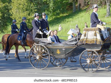 STOCKHOLM, SWEDEN - JUN 06, 2017: The swedish princess and prince Sofia and Carl Philip Bernadotte smiling and waiving to the audience from the royal coach during the swedish national day.