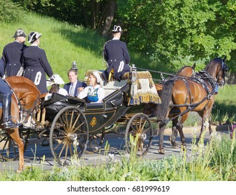 STOCKHOLM, SWEDEN - JUN 06, 2017: The swedish princess and prince Sofia and Carl Philip, Madeleine and Chris Bernadotte waiving to the audience from the royal coach during the swedish national day.