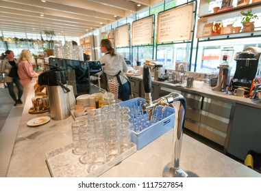 STOCKHOLM, SWEDEN - JUN 14, 2018: Tap of water on counter of city cafe with menu and visitors on June 14, 2018. Sweden with 10,5 million peope ranks high in life expectancy and in safe drinking water