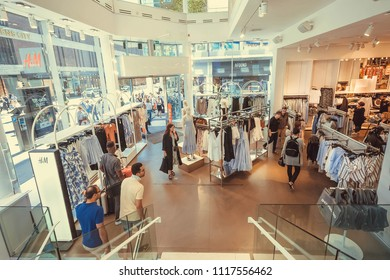 STOCKHOLM, SWEDEN - JUN 14, 2018: Customers buying wear inside popular H&M store with male and female clothes on hangers on June 14, 2018. Sweden with 10,5 million people ranks high in life expectancy