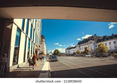 STOCKHOLM, SWEDEN - JUN 14, 2018: Walking people under the concrete bridge in urban area of historical swedish city on June 14, 2018. In the capital of Sweden live 1 million people