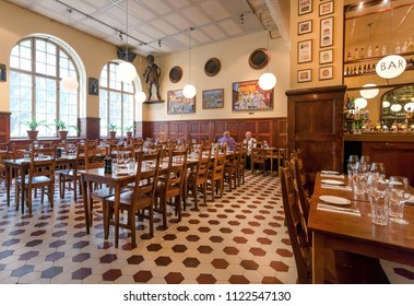 STOCKHOLM, SWEDEN - JUN 14, 2018: Men drinking inside popular restaurant Kvarnen with bar and vintage furniture on June 14, 2018. Sweden with 10,5 million peope ranks high in life expectancy
