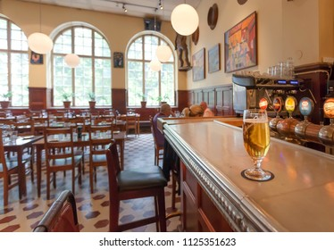 STOCKHOLM, SWEDEN - JUN 14, 2018: Glass of beer on bar counter of the famous restaurant Kvarnen with vintage furniture on June 14, 2018. Sweden with 10,5 million peope ranks high in life expectancy