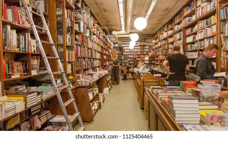STOCKHOLM, SWEDEN - JUN 14, 2018: Readers buying new books inside bookstore with tall bookshelves on June 14, 2018. Sweden with 10,5 million peope ranks high in life expectancy
