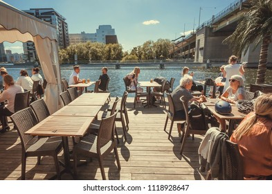 STOCKHOLM, SWEDEN - JUN 15, 2018: Seniors and young people having dinner at river restaurant near the big concrete bridge on June 15, 2018. Sweden with 10,5 million peope ranks high in life expectancy