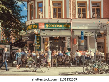 STOCKHOLM, SWEDEN - JUN 15, 2018: Many people having dinner and drinking at outdoor bar on busy street on June 15, 2018. Sweden with 10,5 million peope ranks high in life expectancy