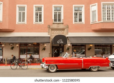 STOCKHOLM, SWEDEN - JUN 16, 2018: Cadillac cabriolet red car in vintage style parked past hotel with relaxing tourists on June 16, 2018. Sweden with 10,5 million peope ranks high in life expectancy