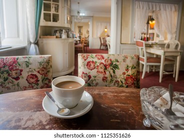 STOCKHOLM, SWEDEN - JUN 16, 2018: Coffee with milk on retro table inside old restaurant with vintage furniture, cozy rooms on June 16 2018. Sweden with 10,5 million peope ranks high in life expectancy