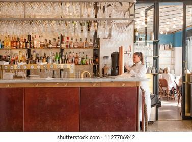 STOCKHOLM, SWEDEN - JUN 16, 2018: Waiter standing near bar couner with alcohol bottles inside modern style restaurant on June 16, 2018. Sweden with 10,5 million peope ranks high in life expectancy