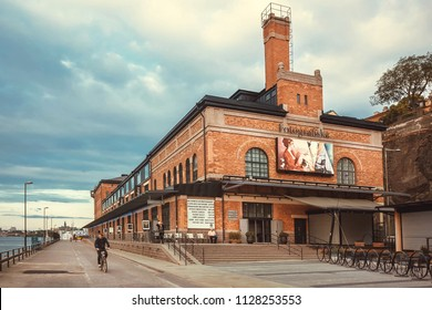 STOCKHOLM, SWEDEN - JUN 16, 2018: Cyclist driving past bilding of the cultural center Fotografiska with brick walls on June 16, 2018. Sweden with 10,5 million peope ranks high in life expectancy