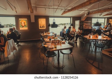 STOCKHOLM, SWEDEN - JUN 16, 2018: People eating food in restaurant with water view, in the cultural center Fotografiska on June 16, 2018. Sweden with 10,5 million people ranks high in life expectancy