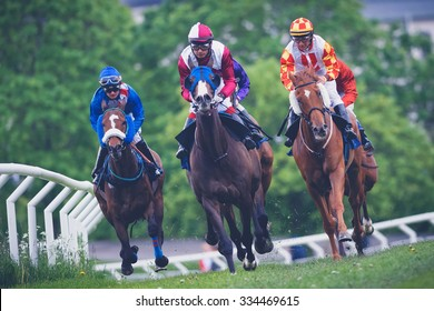 STOCKHOLM, SWEDEN - JUN 6, 2015: Horses with jockeys out of a curve in fast pace at Nationaldagsgaloppen at Gardet. Filters applied