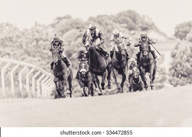 STOCKHOLM, SWEDEN - JUN 6, 2015: Horses with jockeys out of a curve in fast pace at Nationaldagsgaloppen at Gardet. Sepia filter applied