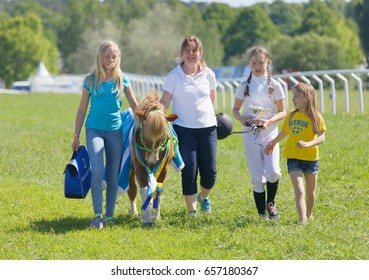 STOCKHOLM, SWEDEN - JUNE 06, 2017: Happy winning jockey of a pony gallop horse race and her proud family at Nationaldags Galoppen at Gardet. June 6, 2017 in Stockholm, Sweden