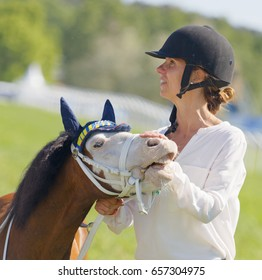STOCKHOLM, SWEDEN - JUNE 06, 2017: Woman strokes a cute pony gallop race horses on the muffle at Nationaldags Galoppen at Gardet. June 6, 2017 in Stockholm, Sweden