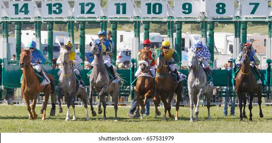 STOCKHOLM, SWEDEN - JUNE 06, 2017: Closeup of the start of the gallop race for arabian race horses and colorful jockeys at Nationaldags Galoppen at Gardet. June 6, 2017 in Stockholm, Sweden
