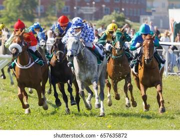 STOCKHOLM, SWEDEN - JUNE 06, 2017: Jockeys on gallop arabian race horses storming ahead at Nationaldags Galoppen at Gardet. June 6, 2017 in Stockholm, Sweden