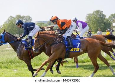 STOCKHOLM, SWEDEN - JUNE 06, 2019: Side view of colorful jockeys riding arabian race horses, audience in the background at ATG Nationaldags Galoppen at Gardet. June 6, 2019 in Stockholm, Sweden